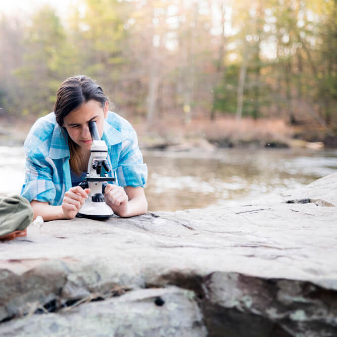 Teenage girl at the edge of a river viewing a water sample through a microscope.